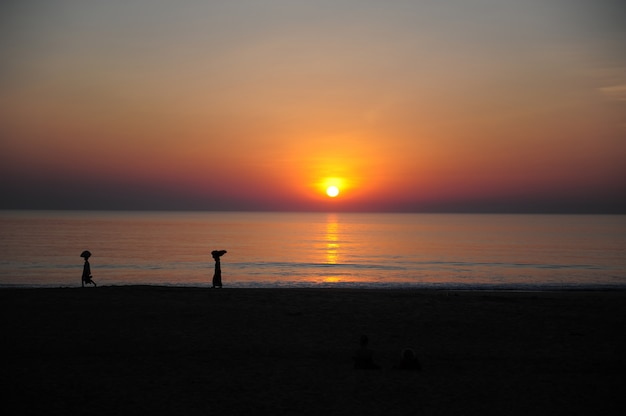 Zonsondergang op de indische oceaan, avondhemel in rode en oranje kleuren. silhouetten van mensen tegen de zee en de ondergaande zon. twilight op de kust in de tropen Premium Foto