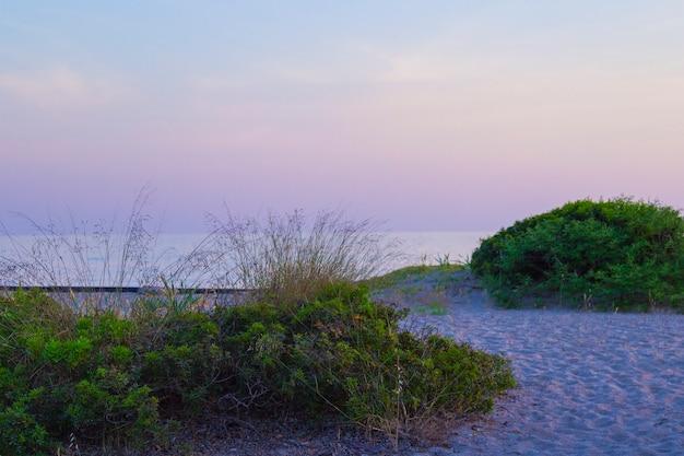 Zonsondergang op het strand met vloeiende felgekleurde stralen van de zon door de wolken Premium Foto