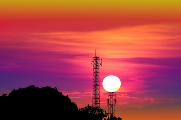 Zonsondergang op kleurrijke avondhemel en silhouet signaal paal Premium Foto