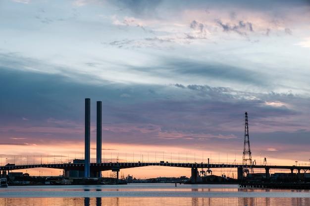 Zonsondergang op zee en brug Gratis Foto