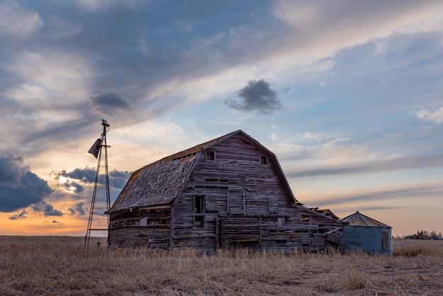 Zonsondergang over een vintage houten schuur, bakken en windmolen in een saskatchewan, canada Premium Foto