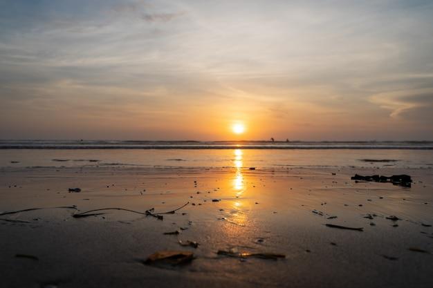 Zonsondergang over een zee met golven die op het strand breken Gratis Foto