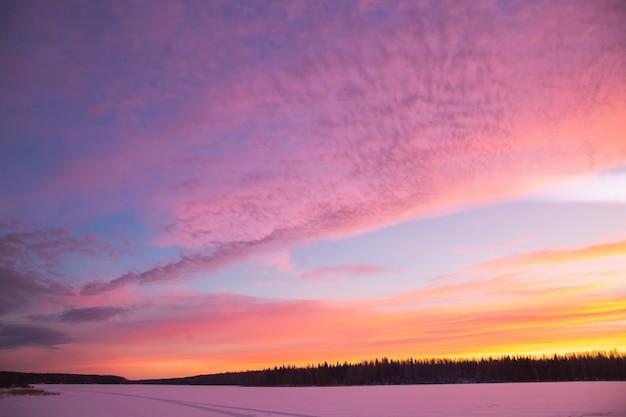 Zonsondergang winterlandschap met besneeuwde weg in violet en roze kleuren Premium Foto