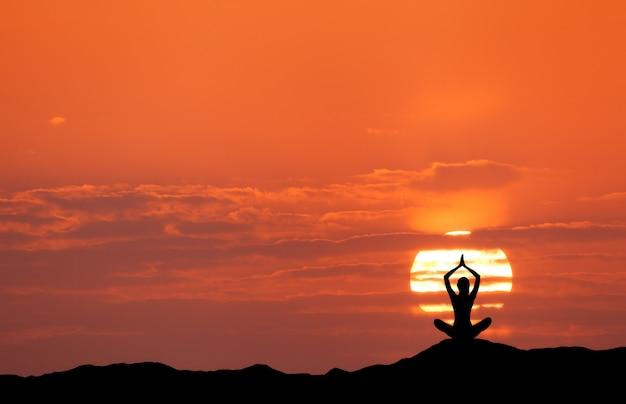 Zonsonderganglandschap met meisje het praktizeren yoga op de heuvel Premium Foto