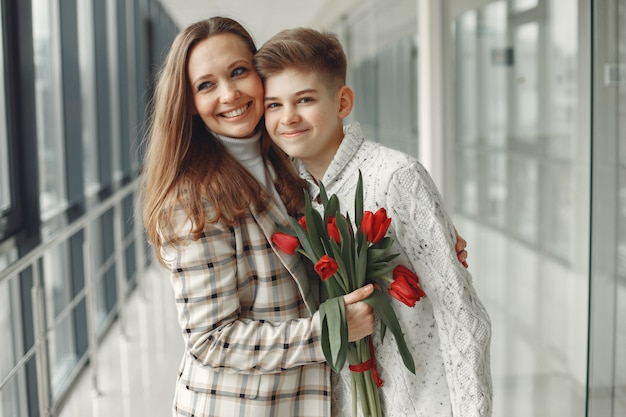 Zoon die een moeder een bos van rode tulpen in moderne zaal geeft Gratis Foto