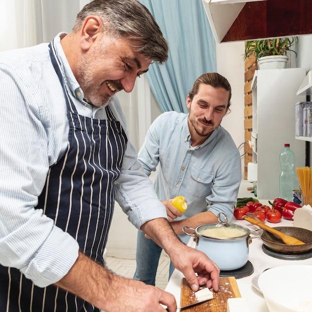 Zoon die zijn vader het koken bekijkt Gratis Foto