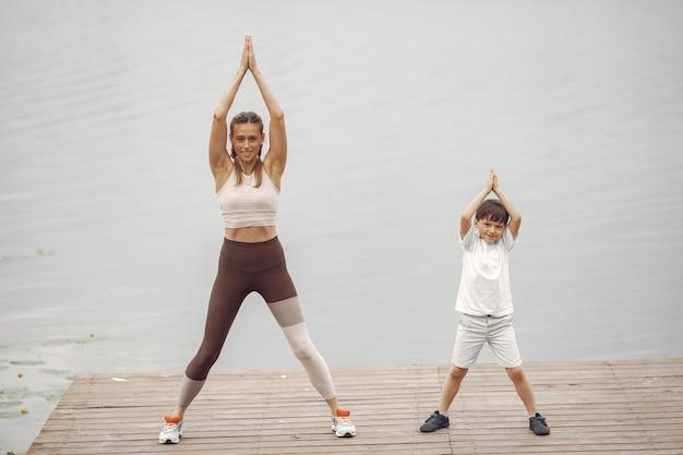 Zoon en moeder doen oefeningen in het zomerpark. familie aan het water. Gratis Foto