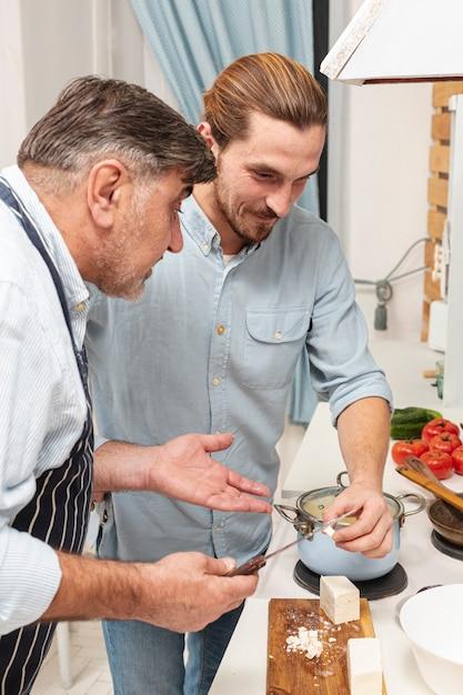 Zoon en verwarde vader koken Gratis Foto