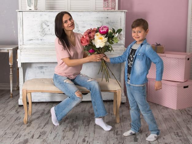 Zoon geeft moeder een boeket bloemen, moederdag concept Premium Foto