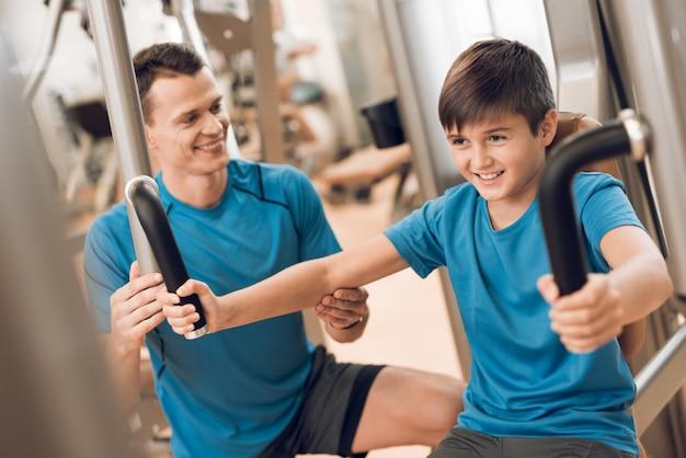 Zoontje voert een oefening uit die papa helpt. Premium Foto