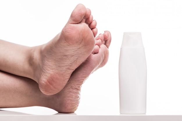 Zorg voor een droge huid op de goed verzorgde voeten en hielen met crèmes Premium Foto