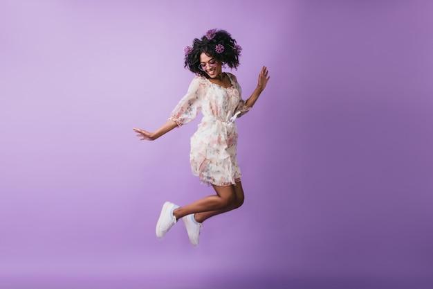 Zorgeloos afrikaans meisje in het witte schoenen springen. aanbiddelijk vrouwelijk model met bloemen in haar die met gelukkige glimlach dansen. Gratis Foto