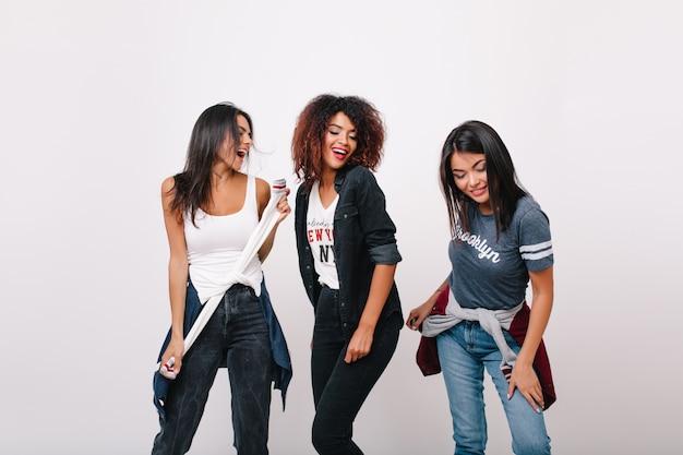 Zorgeloos afrikaans meisje met plezier met modieuze vrienden glimlachen. opgewonden zwart vrouwelijk model dat zich met gesloten ogen bevindt terwijl donkerbruine dames naast dansen. Gratis Foto