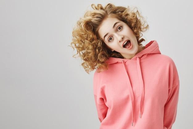 Zorgeloos enthousiast meisje met krullend haar dat haar hoofd kantelt en er verbaasd uitziet Gratis Foto