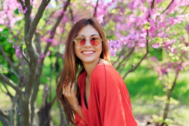 Zorgeloos meisje in stijlvolle strooien hoed en koraal jurk genieten van de lentedag in zonnige tuin op bloeiende boom Gratis Foto