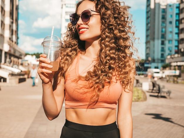 Zorgeloos meisje poseren in de straat met een drankje Gratis Foto
