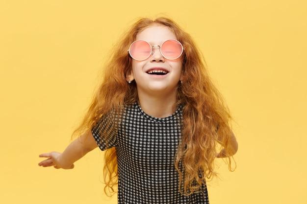 Zorgeloos modieus meisje met krullend rood haar Gratis Foto
