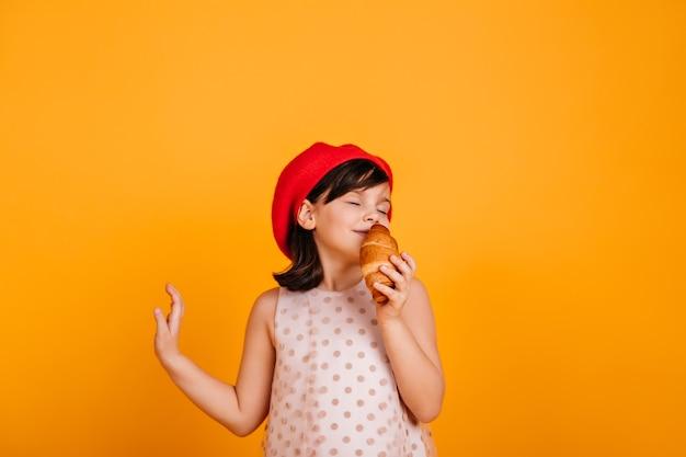 Zorgeloos vrouwelijk kind dat croissant eet. schattig jong geitje dat zich op gele muur bevindt. Gratis Foto