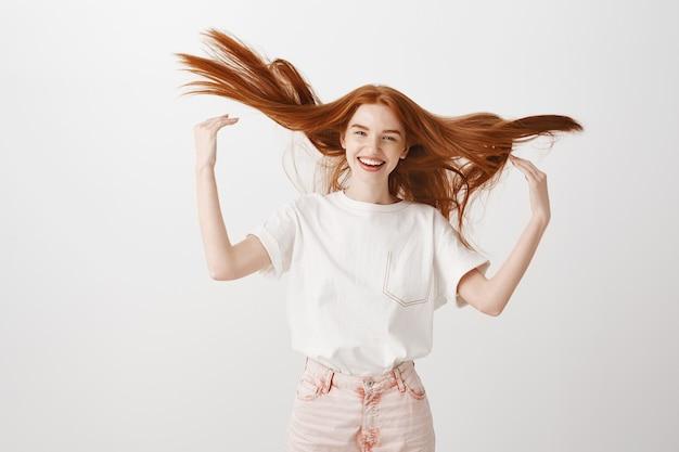 Zorgeloze gelukkige roodharige vrouw die haar haar gooit en vrolijk lacht Gratis Foto