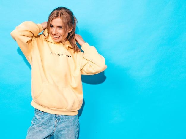 Zorgeloze vrouw poseren in de buurt van blauwe muur in de studio. positief model met plezier Gratis Foto