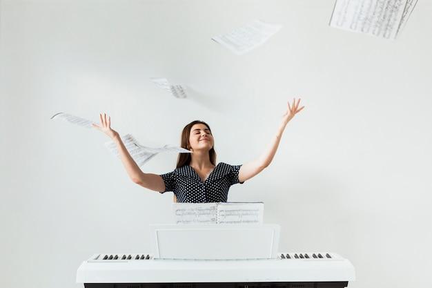 Zorgeloze vrouwelijke pianospeler die de muzikale bladen in de lucht werpen tegen witte achtergrond Gratis Foto