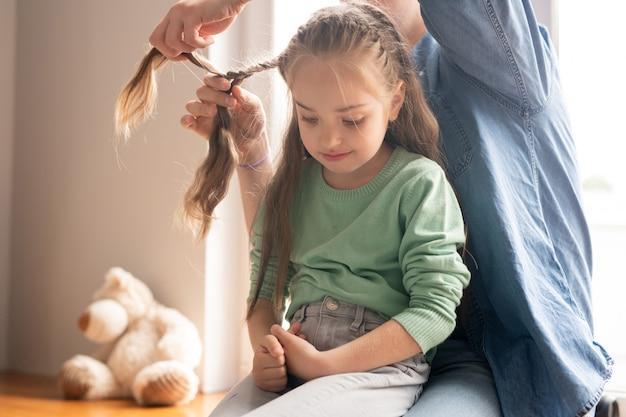 Zorgvuldige jonge vader in denim overhemd vlechten haar van dochter, boos meisje zittend op vaders knieën en naar beneden te kijken Premium Foto