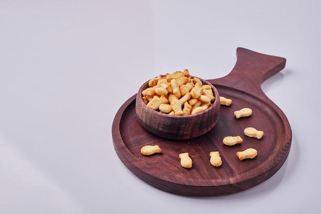 Zoute crackers in een houten kopje geïsoleerd op een grijze achtergrond Gratis Foto