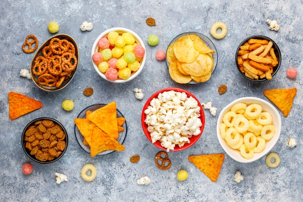 Zoute snacks. pretzels, chips, crackers, popcorn in kommen. ongezonde producten. voedsel slecht voor figuur, huid, hart en tanden. assortiment van snelle koolhydraten Premium Foto