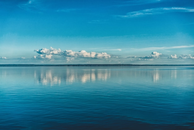 Zuivere witte wolken aan de hemel weerspiegeld in het water van de zee Gratis Foto