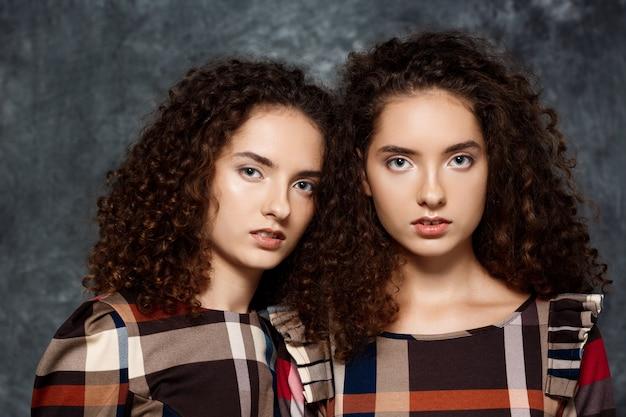 Zusters tweeling die zich voordeed op grijs Gratis Foto