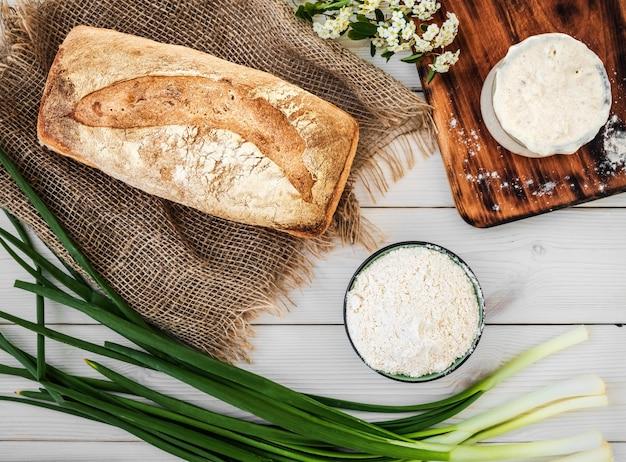 Zuurdesem voor de bereiding van brood, bloem en vers gebakken brood op een witte houten tafel Gratis Foto