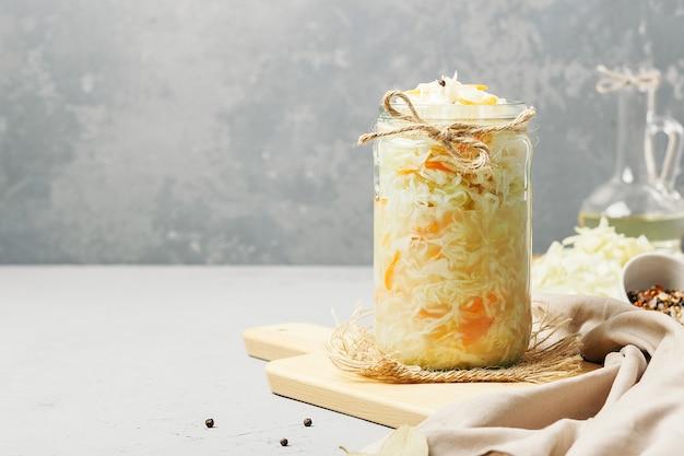 Zuurkool in een glazen pot met ingrediënten op beton met kopie ruimte. Premium Foto