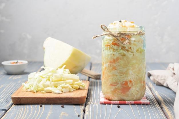 Zuurkool in een glazen pot met ingrediënten op een houten bord. Premium Foto