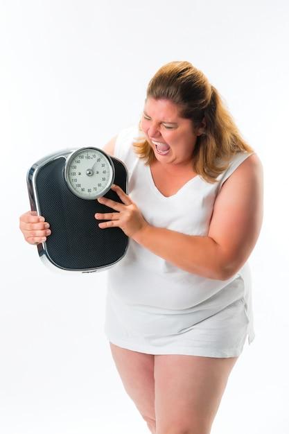 Zwaarlijvige vrouw kijkt boos op schaal Premium Foto