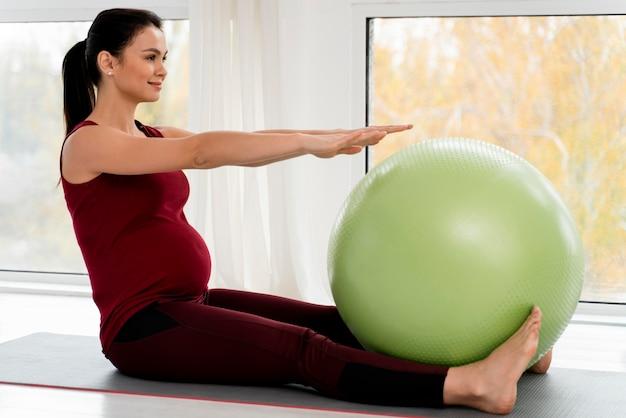 Zwangere jonge vrouw die met geschiktheidsbal uitoefent Gratis Foto
