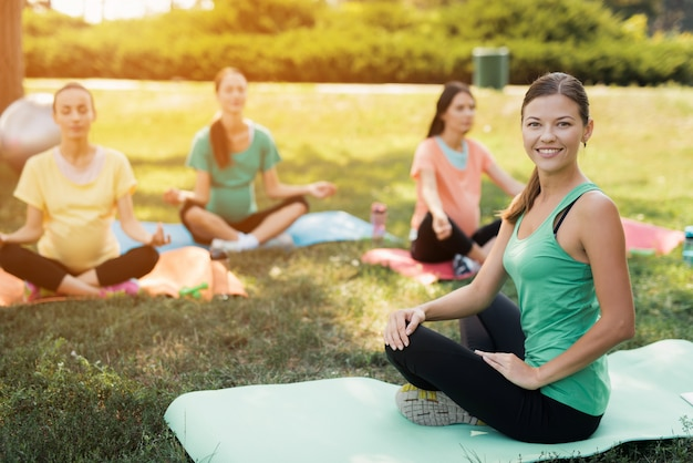 Zwangere meisjes met sporttrainer op yogamatten die yoga doen. Premium Foto