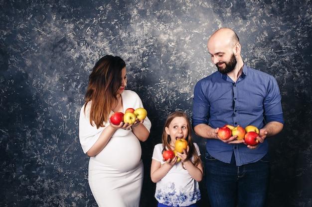 Zwangere moeder, bebaarde vader en dochtertje houden appels in hun handen en willen ze opeten. veganistisch concept Premium Foto