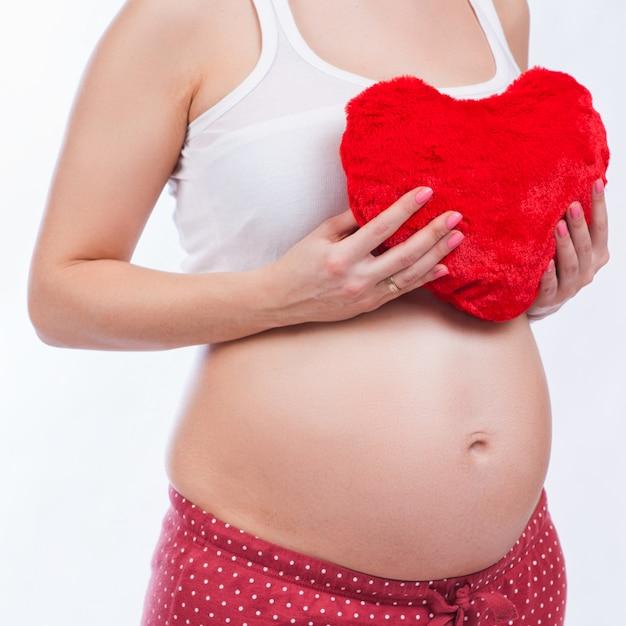 Zwangere moeder die haar buik toont en een stuk speelgoed houdt Premium Foto