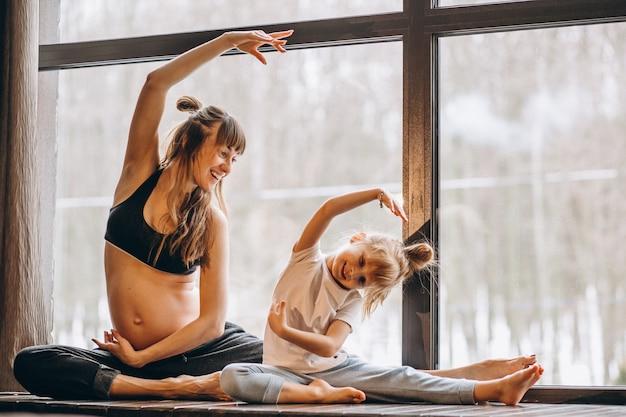 Zwangere mopther die yoga met weinig dochter doet Gratis Foto