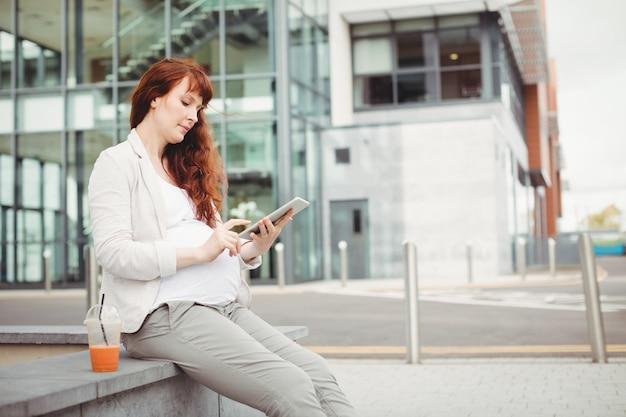 Zwangere onderneemster die digitale tablet met behulp van Gratis Foto