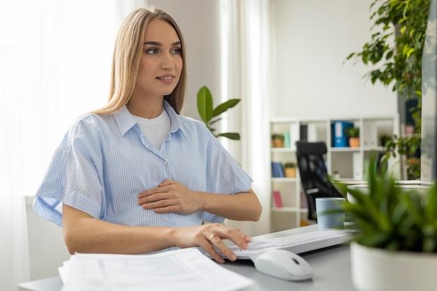 Zwangere onderneemster die op kantoor werkt Gratis Foto
