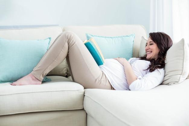 Zwangere vrouw die een boek in woonkamer leest Premium Foto