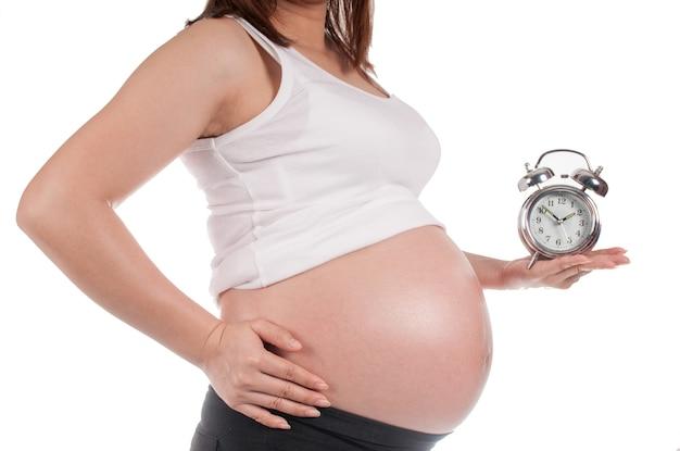 Zwangere vrouw die een klok houdt die op de geboorte wacht Premium Foto