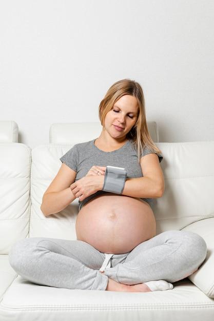 Zwangere vrouw die een medisch hulpmiddel met behulp van Gratis Foto