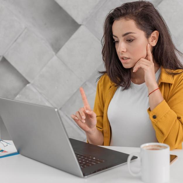 Zwangere vrouw die één ogenblikvinger toont aan laptop thuis Gratis Foto