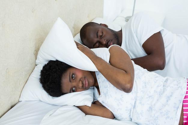 Zwangere vrouw die haar oren behandelt terwijl man het snurken Premium Foto