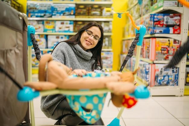 Zwangere vrouw die hangend bed in opslag kiest Premium Foto