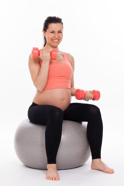 Zwangere vrouw die met domoren uitwerkt Gratis Foto