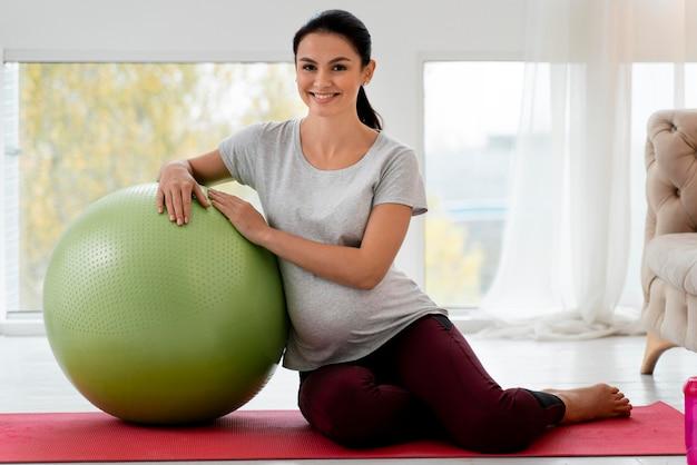 Zwangere vrouw die met geschiktheidsbal uitoefent Gratis Foto
