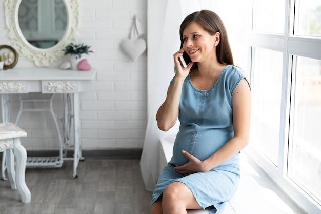 Zwangere vrouw die op de telefoon spreekt Gratis Foto